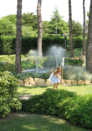 Girl on golf fairway in front of a fountain