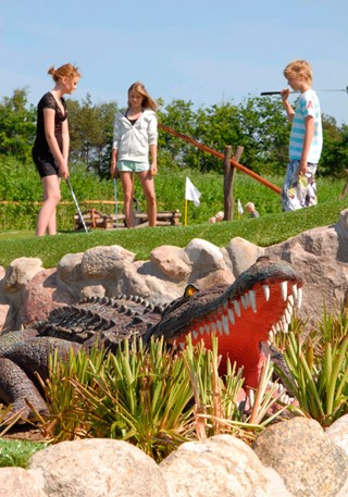 Crocodile in front of kids playing adventure golf