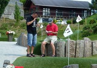 Men counting scores after playing adventure golf