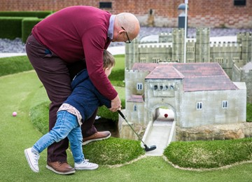 Grandpa playing adventure golf with grand daughter